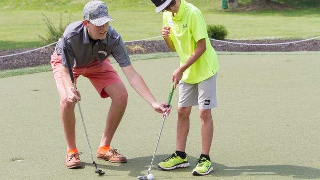 Somerville High School golfer Karl Brand helps Gavin Morrobel, 11, of Scotch Plains with putting at a junior golf clinic co-hosted by the New Jersey Golf Foundation and Middle Atlantic Blind Golf Association. Whippany, NJ. Saturday, June 11, 2016.