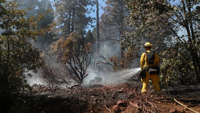 A CalFire firefighter works on one of several small fires Monday east of Shingletown.