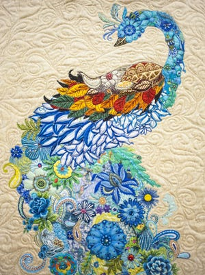 """Festooned in rosette ribbons as a top quilt at the Winter Fair Quilt Show, """"Moment of Rest"""" by Gerri Campbell hangs at Lewistown Art Center."""