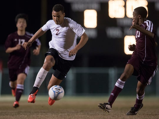 Alabama Christian's J.J. Williams (7)  dribbles past LAMP's Nathaniel Thomas (13) during the match on Tuesday, March 17, 2015, in Montgomery, Ala.