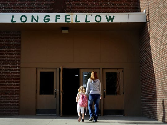 A mother walks her daughter into Longfellow Elementary