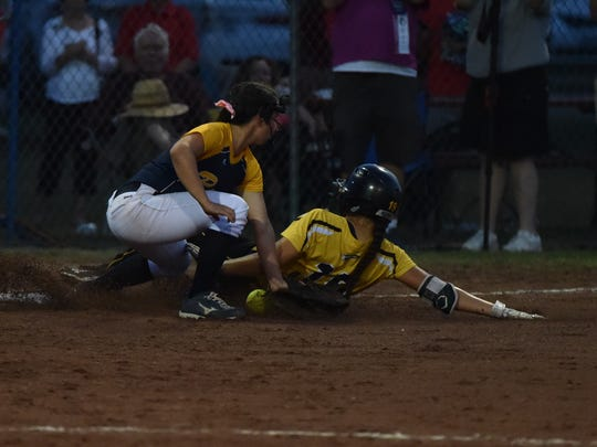 Taryn Swartz of Eddyville-Blakesburt-Fremont slides past Iowa City Regina Taylor O'Conner during the Class 2A championship game on Friday, July 21, 2017.