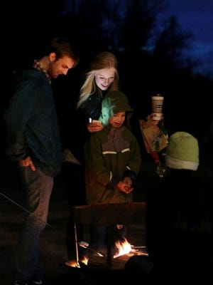 Carter Cottrell, center front, roasts marshallows over a fire with Jeremy Hill, left, and Maria Martin during the Winter Solstice Celebration on Sunday at the Edwin Warner Park Nature Center.