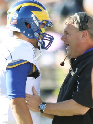 Delaware coach Dave Brock talks to quarterback Trent Hurley during a 2013 game at Navy.