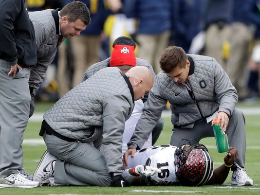 Ohio State quarterback J.T. Barrett (16) is looked at by team officials after being sacked during the second half of an NCAA college football game, Saturday, Nov. 25, 2017, in Ann Arbor, Mich. Barrett did not return after the sack. (AP Photo/Carlos Osorio)