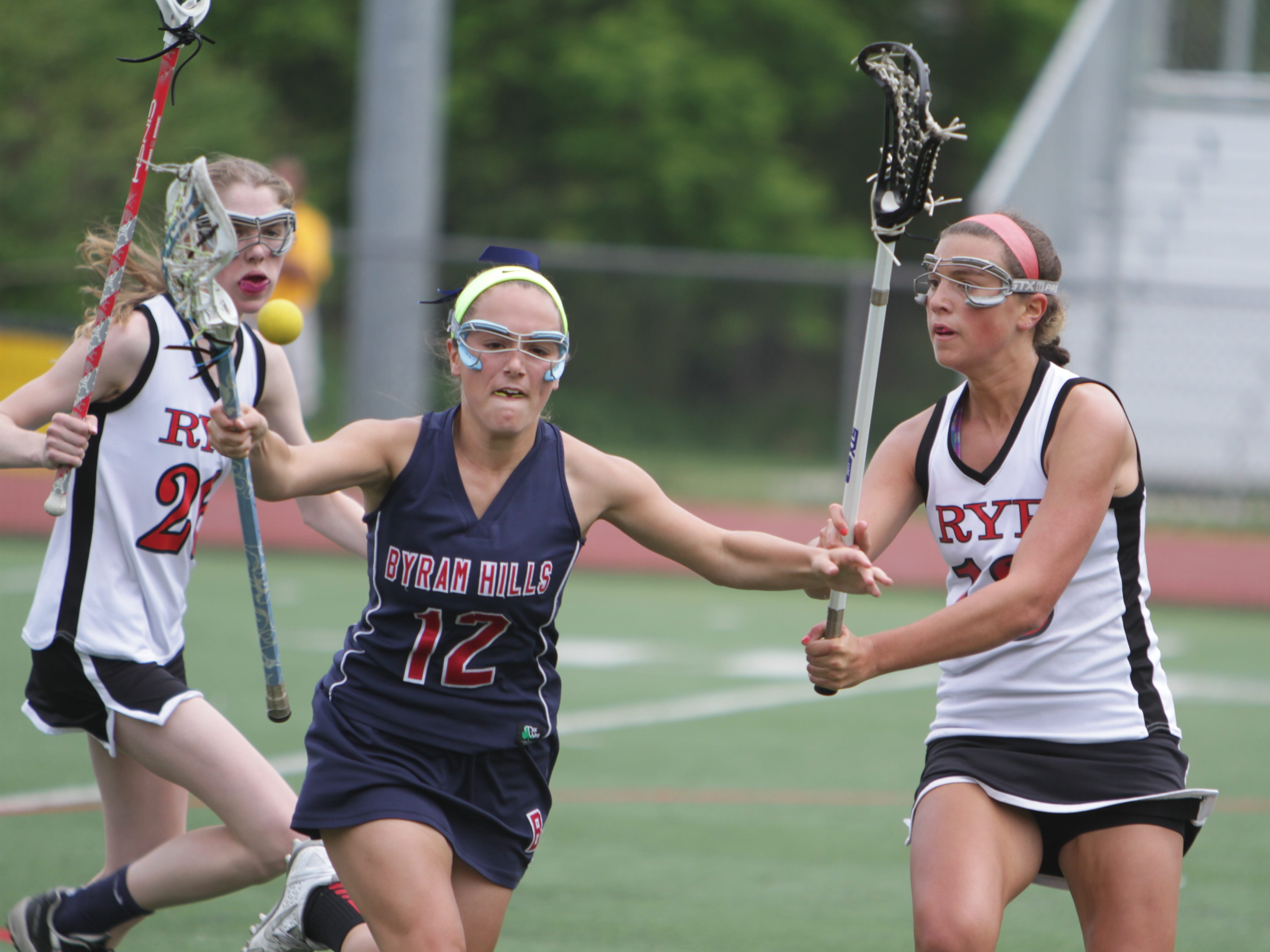 Rye's Charlotte Tucci (13) knocks the ball out of Byram Hills' Taylor Verboys (12) during a Class B quarterfinal game at Rye High School. Rye won 14-10.