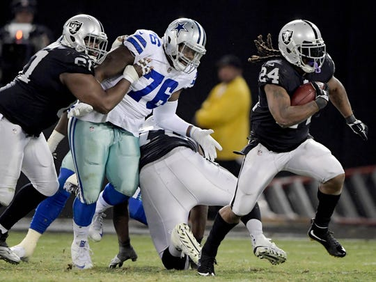 Oakland Raiders running back Marshawn Lynch (24) carries the ball past Dallas Cowboys nose tackle Richard Ash (76) during an NFL football game at Oakland-Alameda County Coliseum.