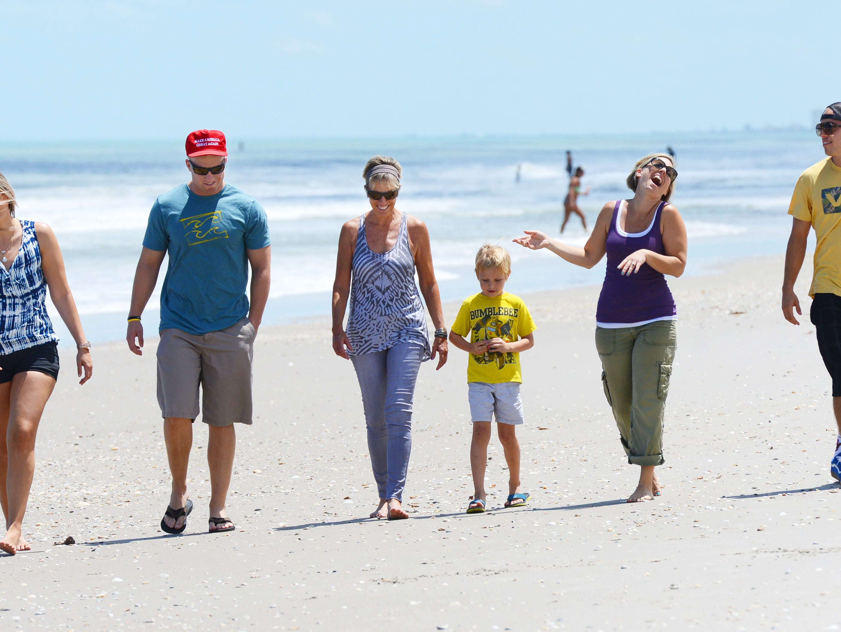 Linda Anderson (center) and her children (from left) Madison Smith, Mason Smith, Anderson, grandson Bodhi Brown, Daughter Tiffany Brown and son Calvin Smith walk the beach in Satellite Beach Saturday afternoon.