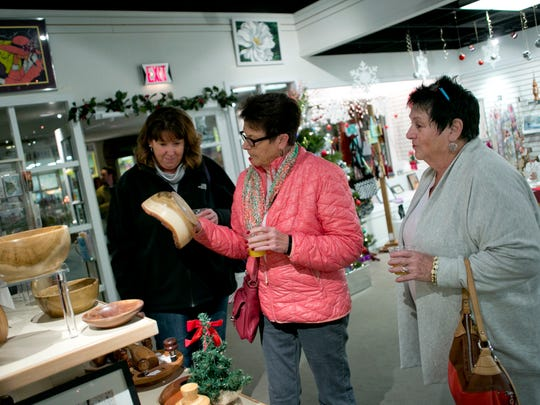 Jody Zimmer, Nancy Zimmer and Margaret Shinske look over items at the St. Clair Art Association while sipping on screwdrivers during the Gourmet Gallop Thursday, Dec. 3, 2015, in St. Clair.