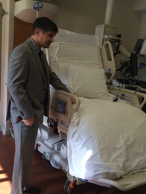 Chuck Brown, executive director of Bethesda-Butler Hospital, shows off a new bed in the freshly expanded intensive-care unit. The official opening for the expanded hospital is Monday.