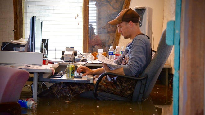 Emile Ancelet, water quality director at Vermilionville, goes through papers Sunday in his flooded office.