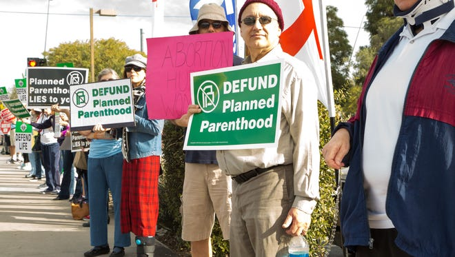 Protesters calling for Planned Parenthood to be defunded rally outside of the Mesa facility on Feb. 11, 2017.