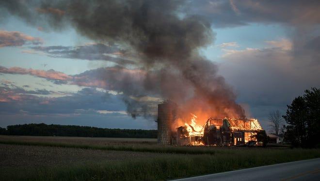 A barn is engulfed in flames Monday night on Elliston-Trowbridge Road.