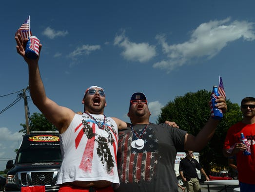 """Miguel Gonzales, left, and J.L. Herrera, right, participate in a cheering contest during the World Cup game between the United States and Belgium at the Budweiser """"mobile sports bar"""" in the parking lot at Main and Broad streets on Tuesday, July 1, 2014."""