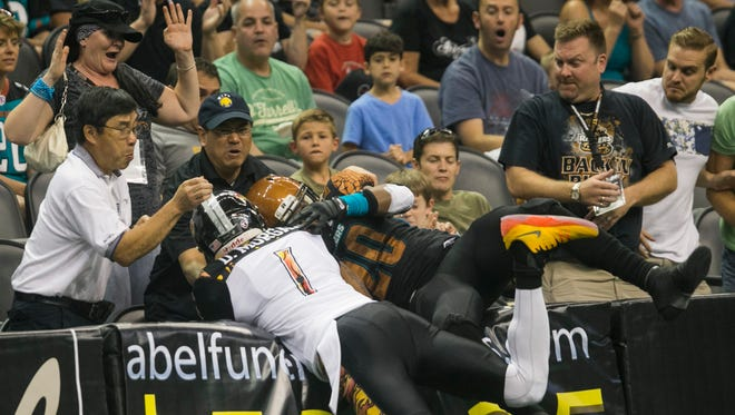 The Rattlers' Jeremy Kellem and the Kiss' Donovan Morgan crash into the stands as they go for the football at US Airways Center in Phoenix on Sunday, July 26, 2015.