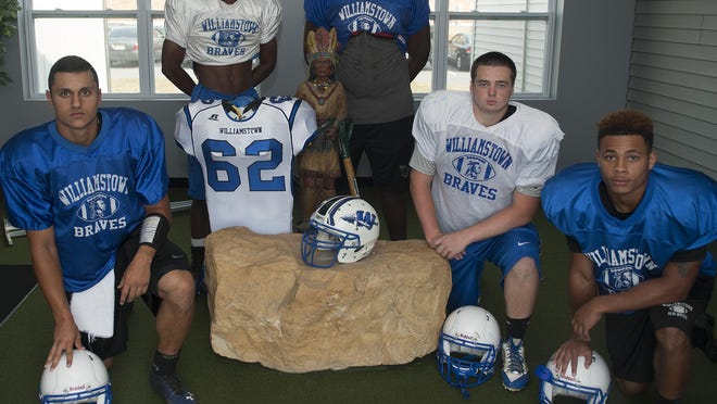 Williamstown Varsity Football Players, Rich Stanzione, Tyrik Glenn, Dondre Dodson, Nick Chamberlin. and Joe Early pose for a portrait next to a memorial for Darius Boyer.