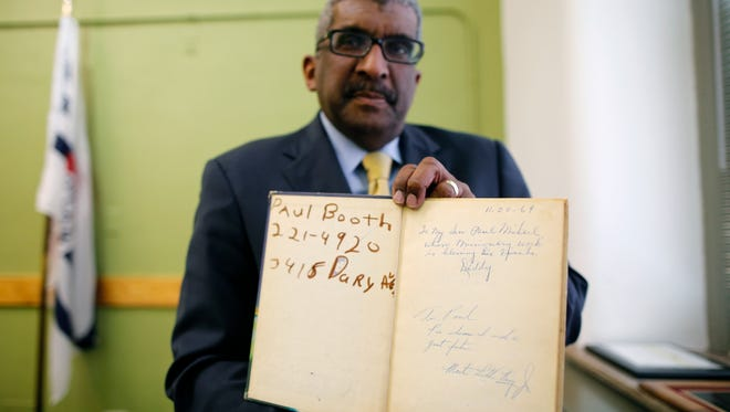 Paul Booth shows a personal note and the signature of Martin Luther King Jr. inside a children's book. King visited the family's home in Avondale in 1964, when Booth was 10 years old.