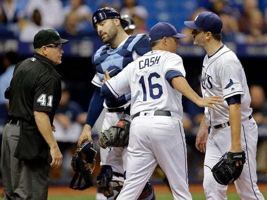 Tampa Bay Rays manager Kevin Cash, second from right, holds back starting pitcher Jake Odorizzi, right, after Odorizzi was ejected by home plate umpire Jerry Meals, left, for arguing balls and strikes during the sixth inning of a baseball game against the Seattle Mariners on Tuesday, June 14, 2016, in St. Petersburg, Fla. Rays catcher Curt Casali is second from left. (AP Photo/Chris O'Meara)
