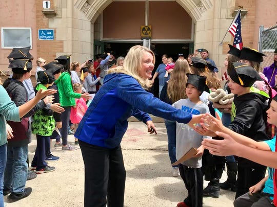 GFPS Superintendent Tammy Lacey gives sixth-graders high fives outside Roosevelt Elementary School.