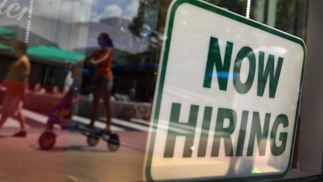 A ''Now Hiring'' sign is seen in the store front window in Miami.
