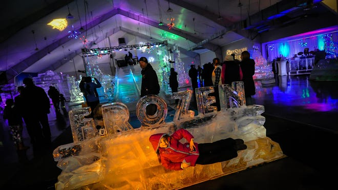 """Brittney Baldwin, of Vernon, lies in front of the Frozen sign at the """"Frozen in Ice"""" event that featured ice sculptures, ice exhibits and ice slides in the exhibit center next to Skylands baseball stadium in Augusta on Feb. 20, 2016. Photo by Jeff Granit"""