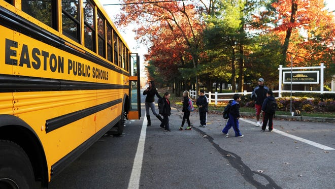 In this November 2013 file photo, adults escort their children from an Easton Public Schools bus on the perimeter of the Easton Crossing condominium development in Easton.