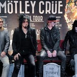 Motley Crue - from left, Vince Neil, Nikki Sixx, Tommy Lee and Mick Mars - pose on mock tombstones at a Los Angeles press conference on Jan. 28, 2014. The band says it will retire in 2015.