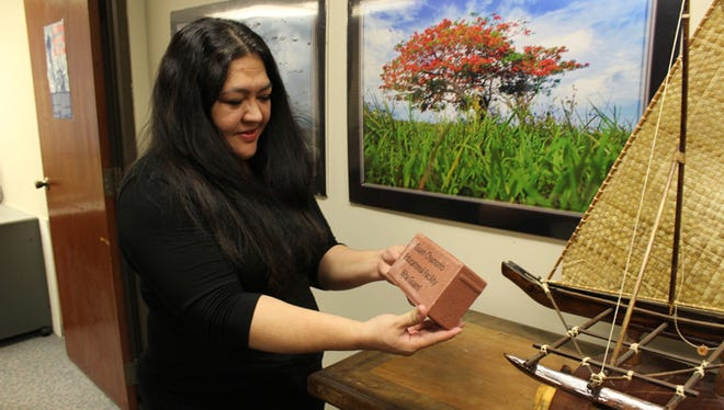 Leona Mendiola Young, director of the Guam Museum Foundation, holds up a brick that is part of the organization's Legacy Brick Program. The fund-raising program allows members of the community to purchase a brick that will be incorporated as part of the structure of the Guam Museum in Hagatna.