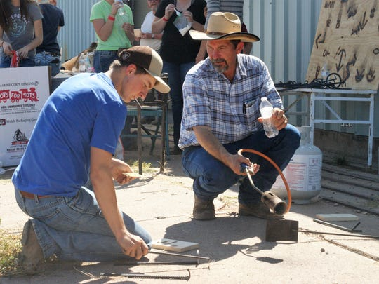 From left, Sam Turner and Deming High School teacher Larry VonTress heat up branding irons on Friday at the Southwestern New Mexico State Fair.