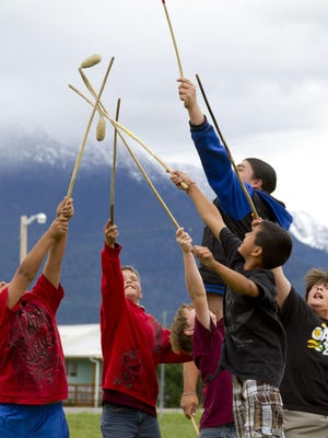 Kids reach to grab the double ball during a match at the Salish Language and Culture Camp. Double ball is a traditional game similar to lacrosse, and is taught to participants of the camp to promote traditions. Thursday, June 20, 2013.