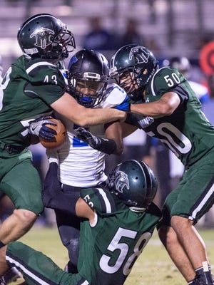 El Diamante's Hudson Walker, left, Enrique Valdez and Alfonso Barba take down Hanford West's Jayron Jenkins in a West Yosemite League high school football game on Thursday, October 12, 2017.