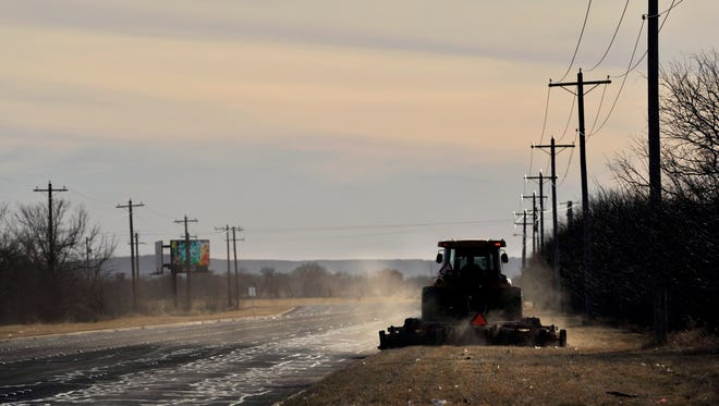 Dust rises from behind a tractor as the driver mows the grass along Southwest Drive Thursday afternoon.