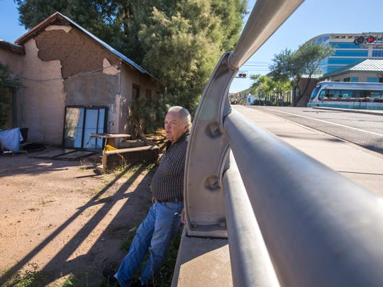 A light-rail train rolls past the property of Steve Sussex on Monday, Oct. 13, 2014. The land appears like a junkyard filled with a couple of hand-made buildings weathered by time, a bus, a cab of a semi-truck, assorted pieces and parts, lumber and bricks. But it is part of his Tempe birthright. Tucked away in the lot is an adobe home, on the corner of Farmer Avenue and 1st Street, that his great-grandfather built in the late 1800s, one the city deems historic. Sussex is battling the state, and will most likely battle the city of Tempe soon, on whether his family gets to keep it.