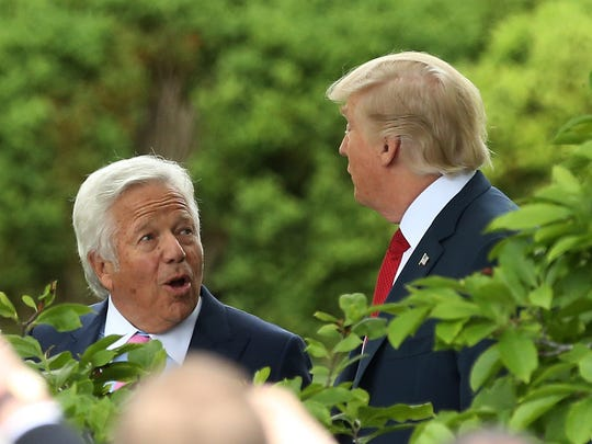 New England Patriots owner Robert Kraft (L) talks with