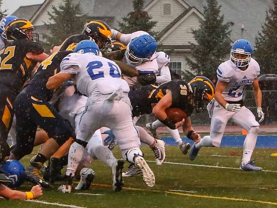 Clarkston's Michael Fleugel (30) gets brought down