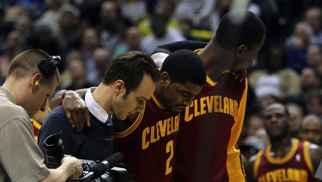 Cleveland Cavaliers point guard Kyrie Irving (2) is helped off the court after being injured during the third quarter against the Indiana Pacers at Bankers Life Fieldhouse.