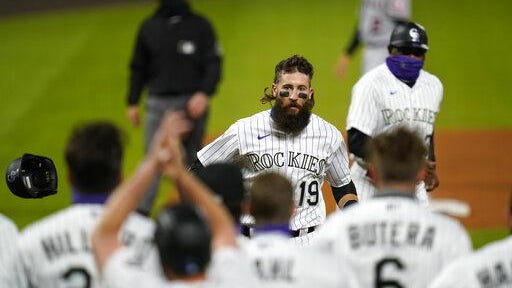 Colorado outfielder Charlie Blackmon, back, circles the bases after hitting a walkoff grand slam off Los Angeles Angels relief pitcher Jose Quijada as teammates wait at home plate to celebrate in the ninth inning on Friday at Coors Field in Denver. The Rockies won 8-4.