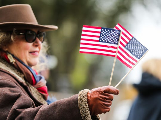 Treva Boyd waves flags and thanks veterans as they pass by in the Lone Star Warriors Outdoors parade Thursday, Dec. 7, along Concho River.
