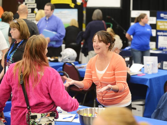 Laura Wisenbarger talks with a visitor to her Randstad Staffing booth at the Zanesville Welcome Center during Thursday's job fair.