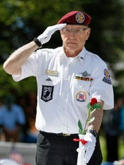 Tom Hoffman sets a flower on the POW/MIA table during a Memorial Day ceremony at the Manitowoc Veterans Memorial Monday, May 29, 2017, in Manitowoc, Wis. The POW/MIA table for one honors fallen, missing or imprisoned military service-members.
