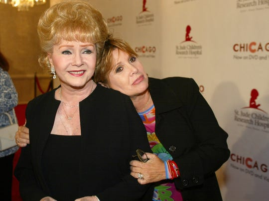 "FILE - In this Tuesday, Aug. 19, 2003 file photo, Debbie Reynolds and Carrie Fisher arrive at the ""Runway for Life"" Celebrity Fashion Show. Reynolds' son said Friday his mother and sister, Fisher, will have a joint funeral and will be buried together."
