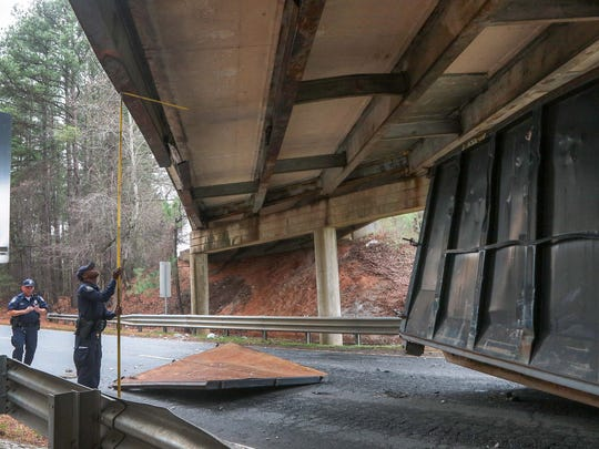 John Lollis, left, officer for the South Carolina State Transport Police, takes a photograph Wednesday of coworker Terrell Praileau, measuring the clearance of the bridge over U.S. 29 North near Williamston.