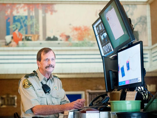 Courthouse security officer Greg Shinkunas stands as he waits for the next visitor by the x-ray machine at Woodbury County Courthouse in Sioux City, Iowa, on Aug. 25, 2015.