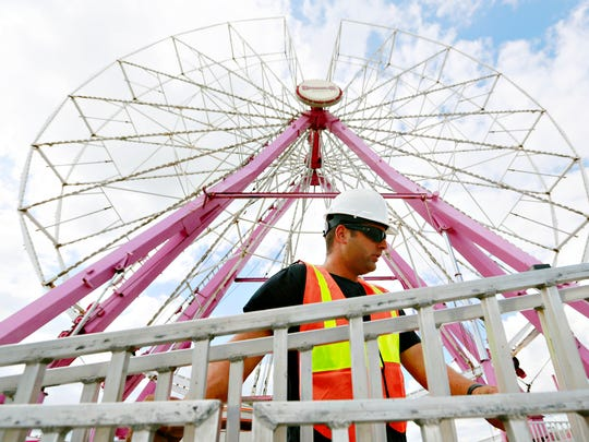 Nick Elliott, of Mason, Michigan, works with a crew to set up the ferris wheel with Deggeller Attractions, based out of Palm City, Fl., as they prepare for York Fair at York Fairgrounds in York City, Thursday, Sept. 7, 2017. York Fair begins Friday, Sept. 8 and runs through Sunday, Sept. 17. Dawn J. Sagert photo
