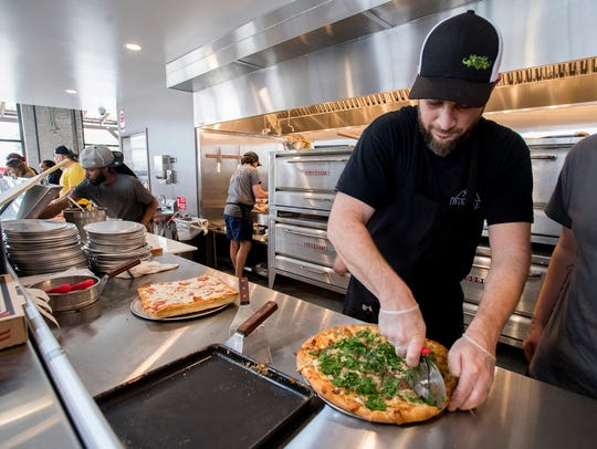 Patrick Walters prepares pizzas as the Common Bond