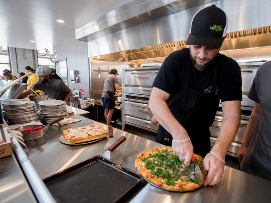 Patrick Walters prepares pizzas as the Common Bond Brewers and Bibb Street Pizza Company hold their official openings in Montgomery, Ala., on Saturday April 14, 2018.