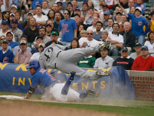 Milwaukee Brewers pitcher Yovani Gallardo (49) is upended