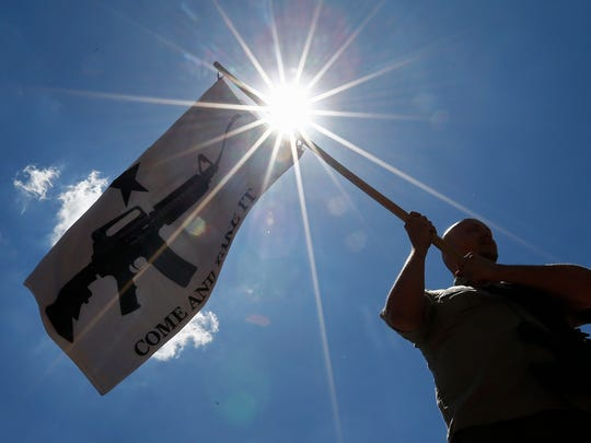 A man holding a Come and Take It flag joins other people during a open carry rally outside the Kay Bailey Hutchison Convention Center on the second day of the NRA Annual Meetings.