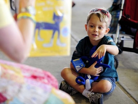 Holding a stuffed 'Pete the Cat' toy, Giovanni Silimperi, 5, of Manchester Township, listens as storyteller Miss Ellen reads aloud the book 'Pete the Cat' at Sovereign Bank Stadium on Saturday. (DAILY RECORD/SUNDAY NEWS -- CHRIS DUNN)