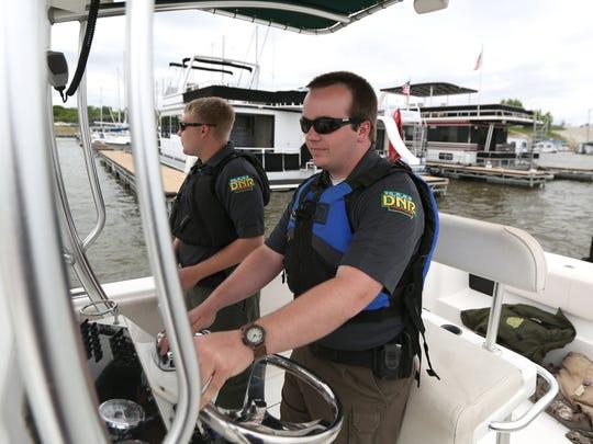Matt Merrick of the Iowa Department of Natural Resources navigates a patrol boat around boats moored at the Saylorville Marina at Saylorville Lake on Saturday, May 23, 2015.